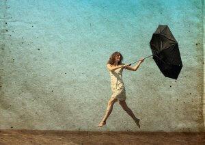 fröhliche Frau mit Schirm im Gegenwind