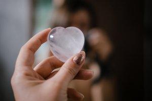 eine Frau hält ein Herz aus Rosenquarz. Selbstliebe.